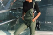 a black crop top, an olive green dungaree, white sneakers and a black crossbody for a comfortable and sexy spring look