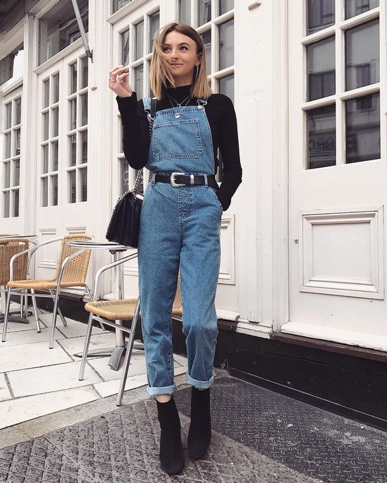 a black turtleneck, a blue denim dungaree, black heeled booties and a black bag to wear this spring