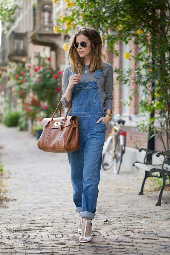 a spring outfit with a grey top, a blue shaggy denim overall, white shoes and a large brown bag