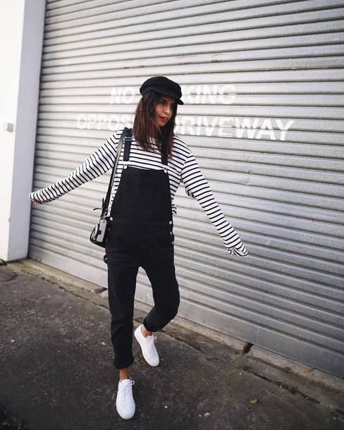 a striped black and white top, a black dungaree, white sneakers and a black crossbody for a monochromatic spring look