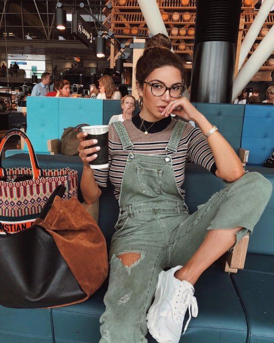 a striped top, a green ripped dungaree, white trainers and a two tone bag is a trendy spring look