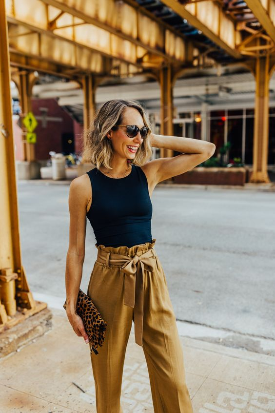 a black sleeveless top, mustard-colored paperbag pants and a leopard clutch for hot summer days