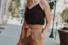 a black spaghetti strap top, rust-colored paper bag pants and a woven bag for a summer look