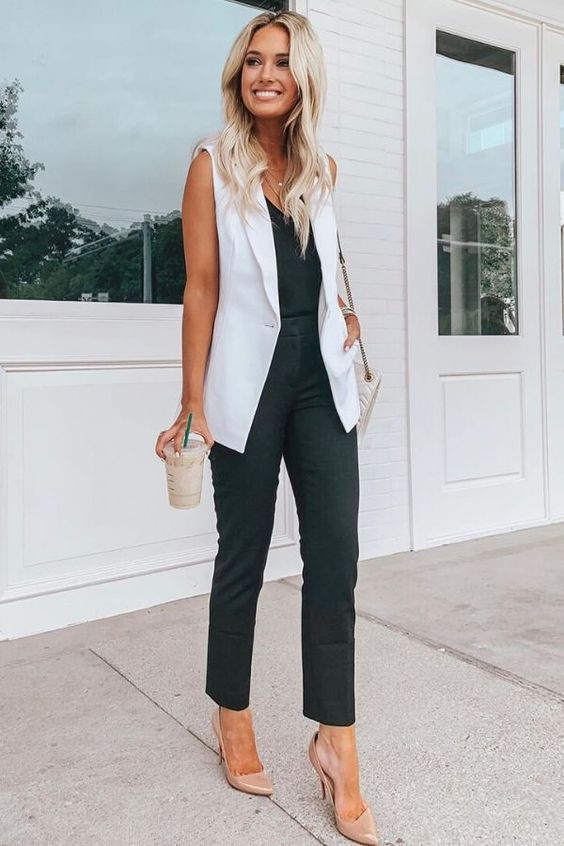 a black top, black pants, a white sleeveless blazer, blush shoes and a white bag for working in summer