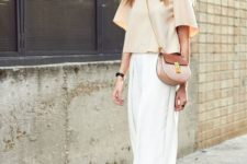 a light yellow crop top with wide sleeves, white culottes, tan block heels and a two tone bag