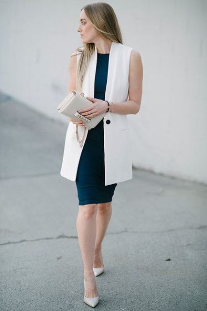 a navy knee fitting dress with no sleeves and a high neckline, a long sleeveless blazer and white shoes plus a neutral clutch