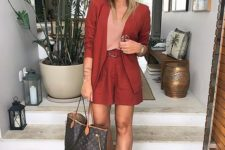 a red suit with shorts, a blush top, tan trainers, a brown tote for a bold summer work look