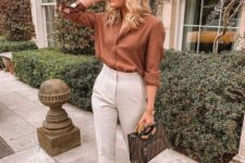a rust-colored shirt, white high waisted pants, white mules and a printed bag