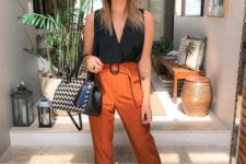 a stylish look with a black sleeveless top, orange cropped pants, black lace up shoes and a printed bag