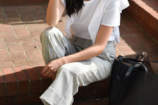 a white blouse with ruffle sleeves, grey cropped pants, grey shoes and a black tote for a monochromatic look
