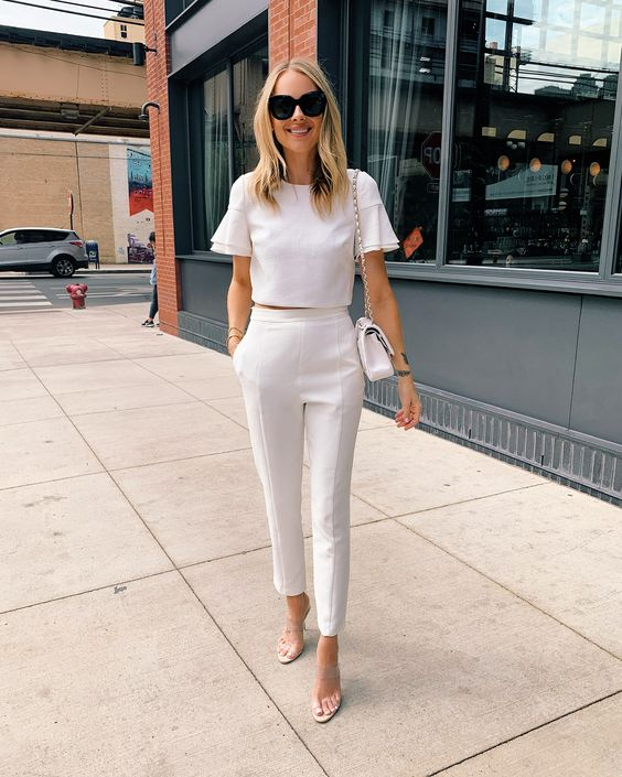 a white crop top with ruffle sleeves, white pants, tan shoes and a white bag