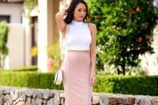 a white halter neckline crop top, a blush fitting midi skirt, white heels and a creamy bag