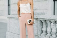 a white spaghetti strap top, blush pants, a white whimsical clutch and statement earrings