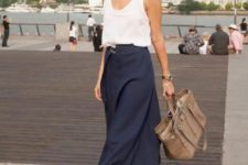 a white tank top, a navy A-line midi, printed shoes and a tan tote for a hot summer day