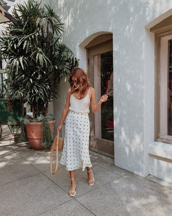 a white top, a polka dot fit and flare midi, white square toe shoes and a brown bag