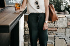 an off-white sleeveless shirt, black pants, rust-colored shoes and a brown leather tote