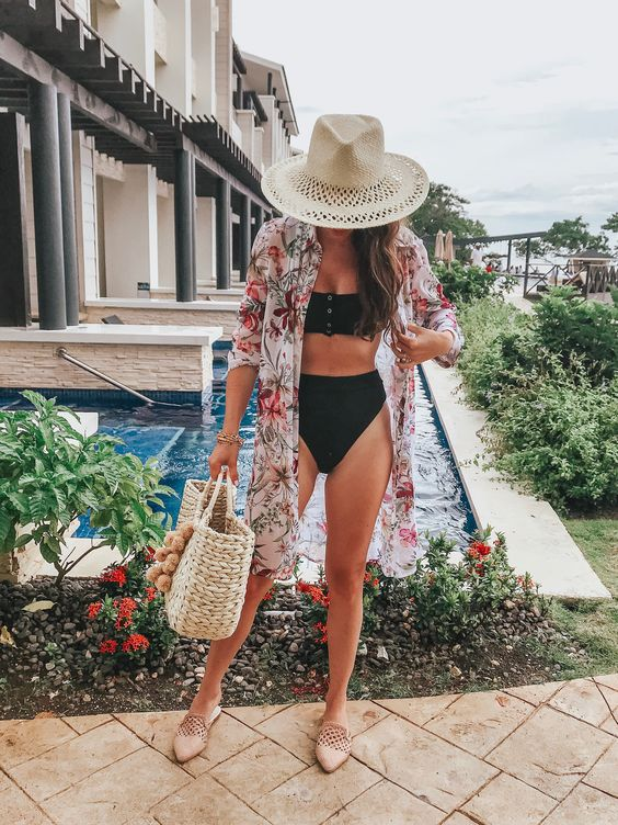 a black bikini and a colorful floral coverup and blush mules for a trendy beachy outfit