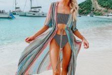 a colorful vertical stripe beach kimono and a striped modern bikini make up a bold and fun look