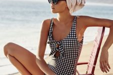 a retro-inspired black and white plaid one piece swimsuit with ties on the front