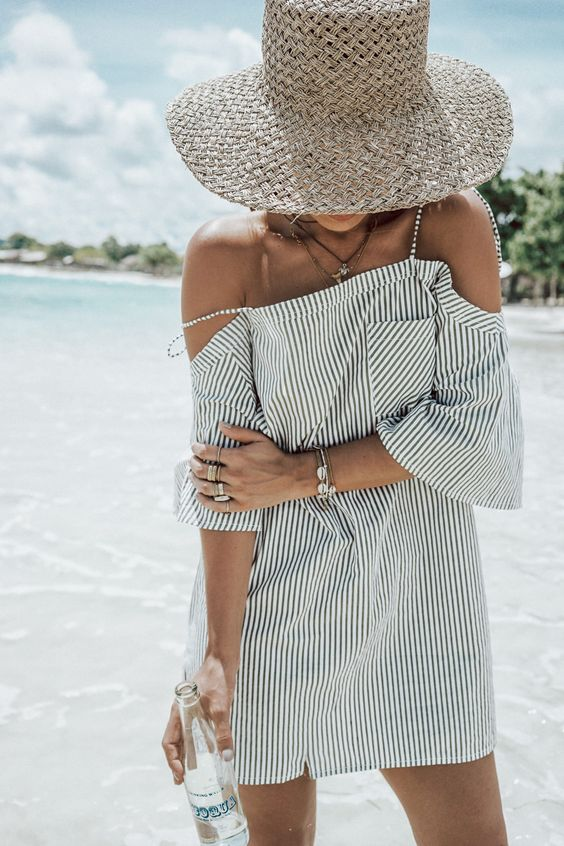 a striped black and white mini dress with a cold shoulder looks very beach-like