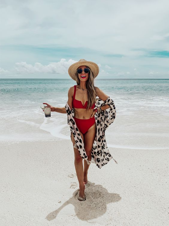 a white bikini with a high waisted bottom and a leopard print coveurp, a red lip and a hat for a bold look