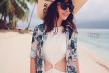 a white one piece cutout onokini and a pink coverup with a tropical leaf print plus a wide brim hat