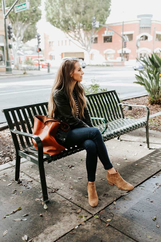 a casual look with navy skinnies, a striped top, a black leather jacket, ocher ankle booties and a cognac tote