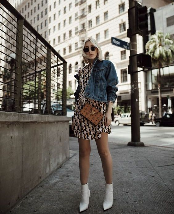 a printed over the knee dress, a cropped dehim jacket, white ankle booties and a crossbody bag