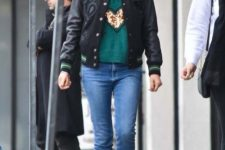 an embellished green sweatshirt, blue skinnies, a black bomber jacket and black combat boots
