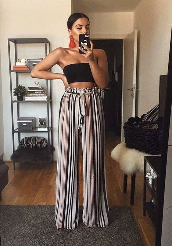 a black crop top, striped palazzo pants, red statement earrings for a bold and trendy look