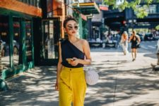 a black one shoulder top, sunny yellow pants, shiny shoes and a white basket bag for summer