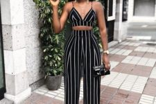 a black striped crop top and high waisted palazzo pants, white statement earrings and layered necklaces