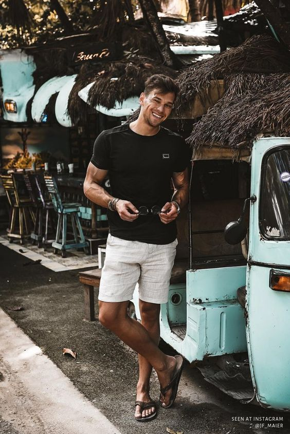 a black tee, white linen shorts and black flipflops for a cool holiday look with no effort