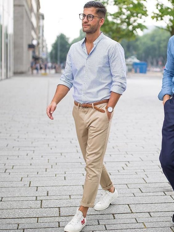 a blue striped shirt, tan chinos and white sneakers to create a comfortable casual look for work