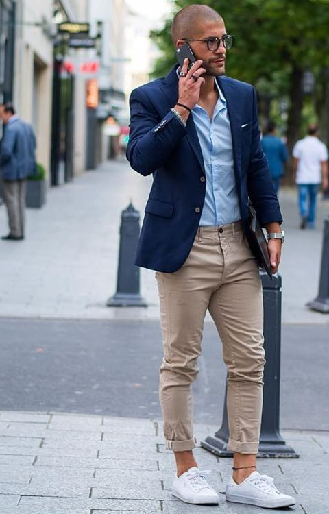 a casual work outfit with a blue button up, a navy jacket, tan chinos, white sneakers