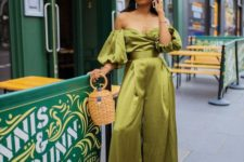 a chic green silk off the shoulder jumpsuit with puff sleeves and wide pants, a basket and a hat