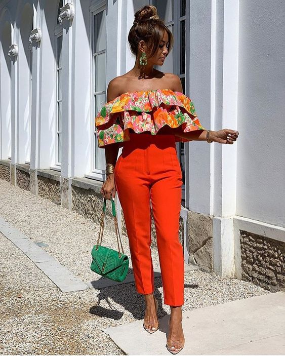 a colorful floral off the shoulder ruffle top, orange high waisted pants, acrylic heels and a green bag