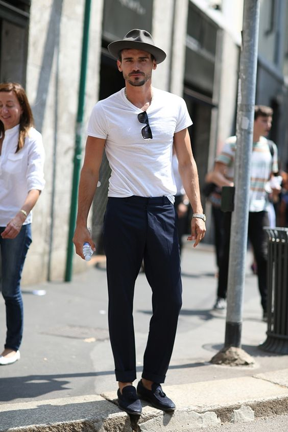 a relaxed summer work look with a white tee, navy pants, navy moccasins, a grey hat and sunglasses