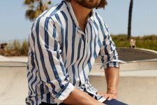 a striped blue and white shirt and navy shorts are seaside classics to go for