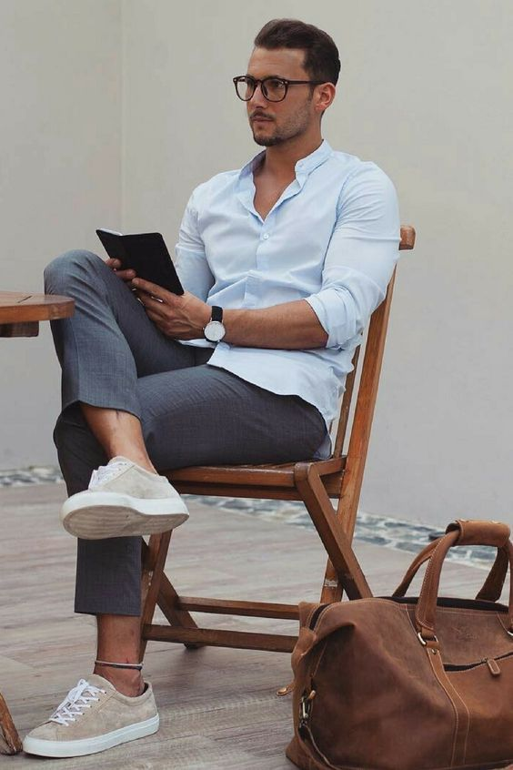 a stylish work outfit with a light blue shirt, grey cropped pants, neutral sneakers and a brown bag