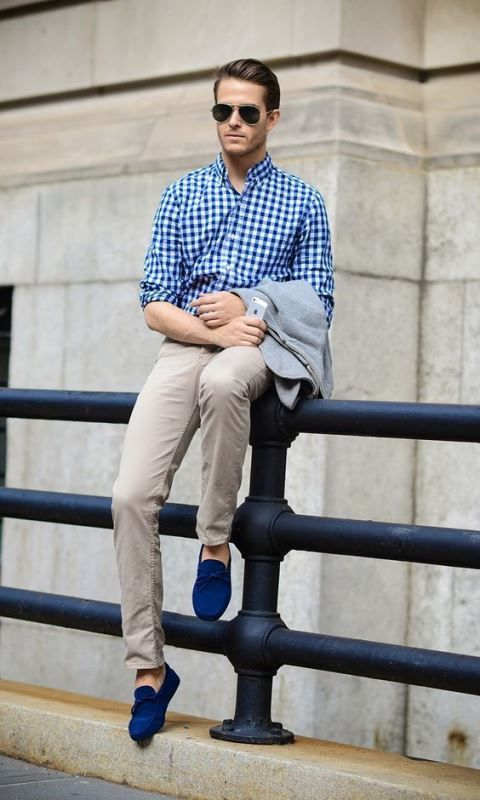 a trendy men outfit with bright blue loafers, a checked blue shirt, tan pants and a grey blazer