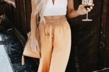 a white crop top with a cut, chic rust-colored palazzo pants, a matching bag and large sunglasses
