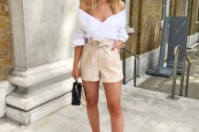 a white off the shoulder top, tan high waisted shorts, acrylic mules and a black bag