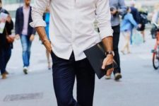 a white shirt, navy pants, black shoes and a black hat for a creative summer work look
