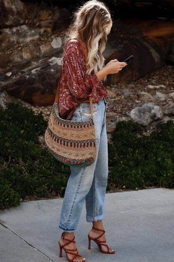 a burgundy floral oversized shirt, blue jeans, burgundy strappy heels and an embroidered tote
