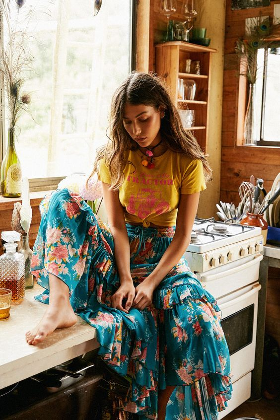 a colorful summer boho outfit with a yellow printed tee and a navy floral ruffle midi skirt