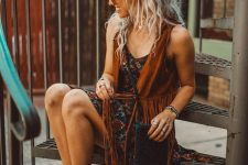 a printed mini dress, a suede fringe waistcoat, brown strappy sandals and a small woven bag with tassels