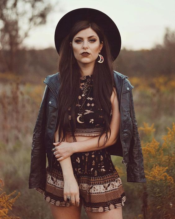 a statement summer to fall boho look with a black suit with a crop top and shorts, a black leather jacket and a hat