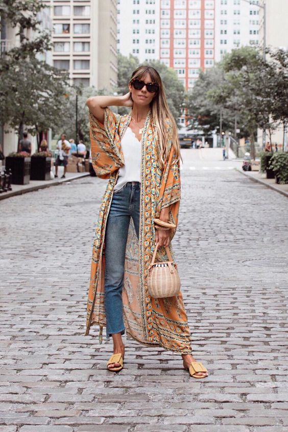 a stylish boho look with a white tee, blue jeans, yellow slippers, a woven bag and a floral print kimono