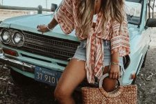 a white bra top, denim shorts, a red and white printed shirt, silver slippers and a straw bag